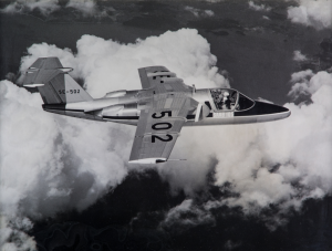 A black & white image showing the Second Saab 105 prototype mid-flight. The aircraft is mostly unpainted, while carrying civilian markings.